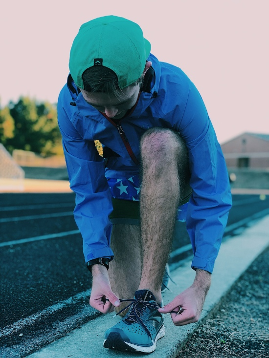 Nathan Galloway, a Piedmont College distance runner, laces up before a tack workout at Wilbanks.