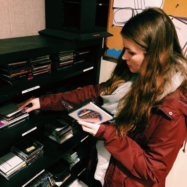 After Marion is finished with her script, she can go to finding music she needs for the theme of the show she is producing. Marion is looking through CD's in the studio and trying to find Christmas genre music for the listeners to get into the Christmas spirit.