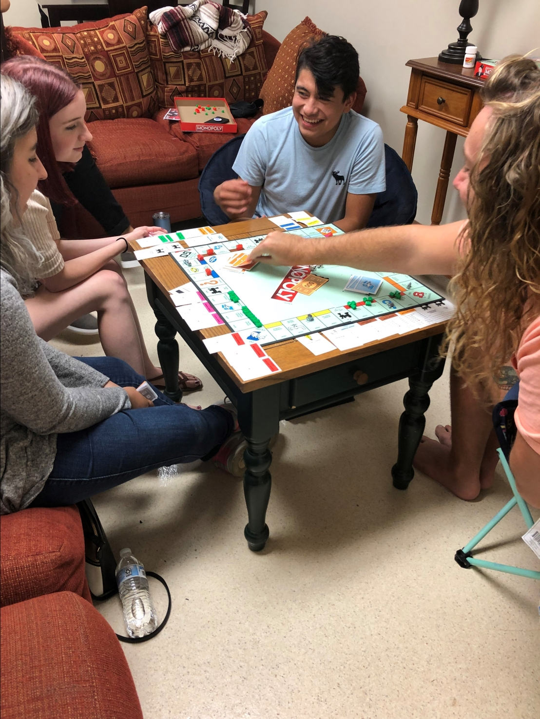 Poala Trujillo (left) Jena Conley (Left red hair) Kobhe Macias (middle) and Sean Ogle enjoy a game of Monopoly.