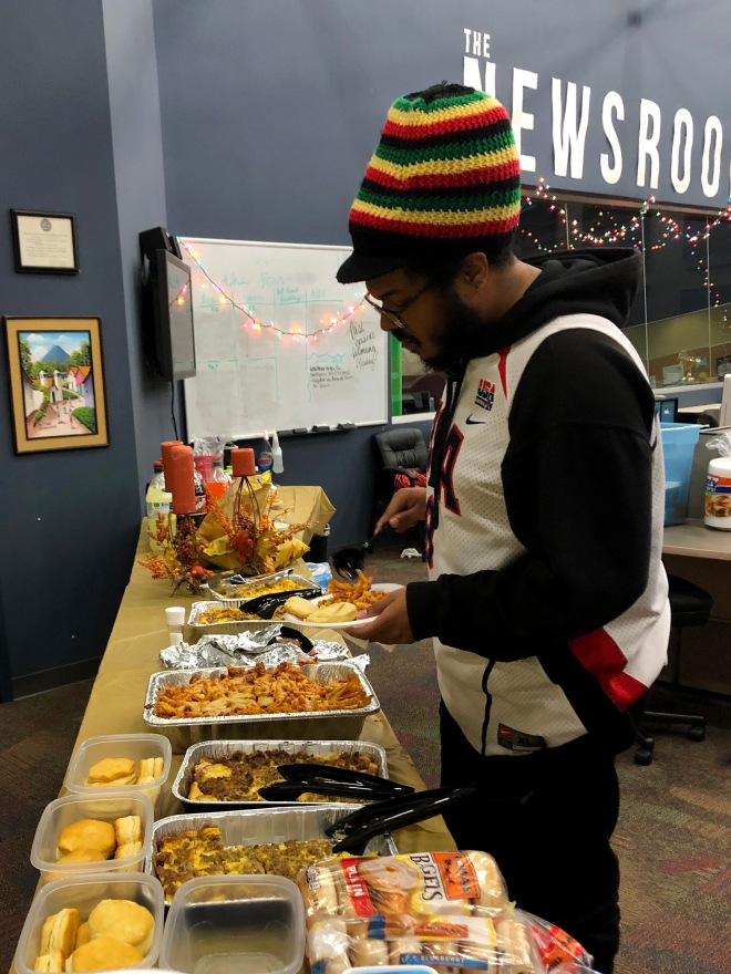 "Mass communications graduate assistant Amin Abraham-Quiles makes his plate at the department ""Friendsgiving."" The department's students and faculty gathered at the Swanson Center Newsroom to enjoy food, friendship and holiday radio shows. PHOTO / Nate Roys"